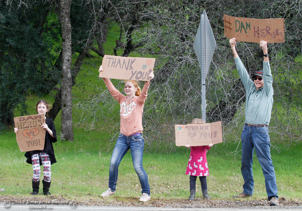 . Alana McBave, 7, Emma Garrahy, 13, Brooke McBave, 5, and Bob Lowdermilk wave thank you signs at the intersection of Canyon and Royal Oaks Drive where trucks carrying boulders to the emergency spillway are in continuous rotation February 16, 2017 in Oroville, California. (Emily Bertolino -- Enterprise-Record)