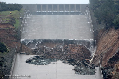 The hole from the damaged Oroville Dam controlled Spillway is seen prior to the water release on Thursday. The hole continues to grow larger as water is released Thursday Feb. 8, 2017.  Erosion along the left side continues to increase as the spillway falls apart. (Bill Husa -- Enterprise-Record)