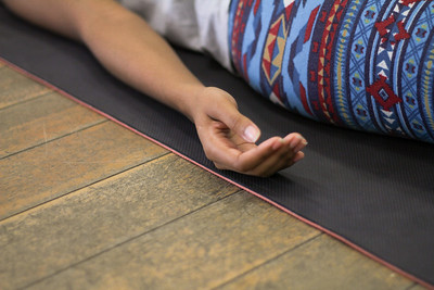 Person in Savasna with Hand Resting on a Black Yoga Mat