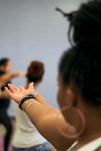 Black Woman with Hand Outstretched in a Yoga Class