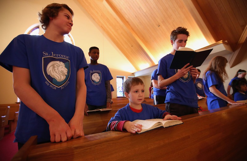 9:45 a.m. St. Jerome Catholic School, Maplewood: From left, 8th-grader Sean Smith, kindergartner Justin Knauss & 8th-grader Josh Tell sing at the start of Mass.