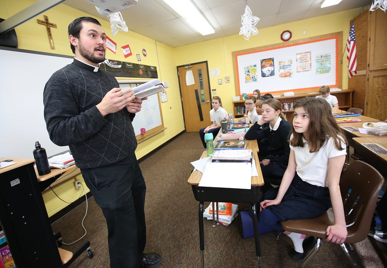 1:45 p.m. Holy Name of Jesus, Medina: Father Spencer Howe, associate pastor, talks to sixth-graders Jan. 18 at Holy Name of Jesus School, including Rachel Heinz, right.