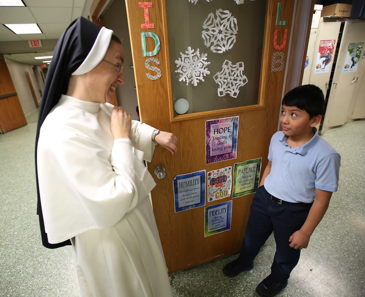 8 a.m. St. Croix Catholic School, Stillwater: Sister Mary Juliana Cox, principal, talks with a student.
