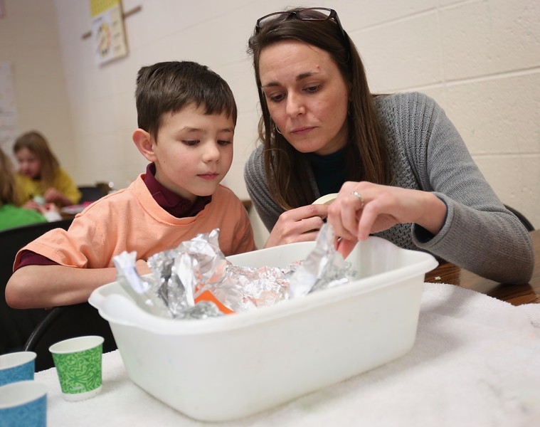 12:46 p.m. Good Shepherd School, Golden Valley: A preschooler gets help from his teacher.