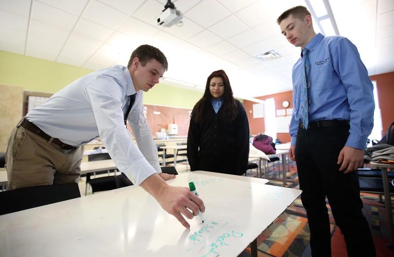 11:29 a.m. Cristo Rey Jesuit High School, Minneapolis: Students and teacher plan an activity.