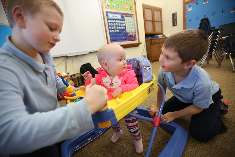 3:05 p.m. St. Timothy, Maple Lake: 2nd-grader Tucker Sigler, left, & kindergartner Akeley Christenson play with Natalie, daughter of teacher Alyssa Sernett.