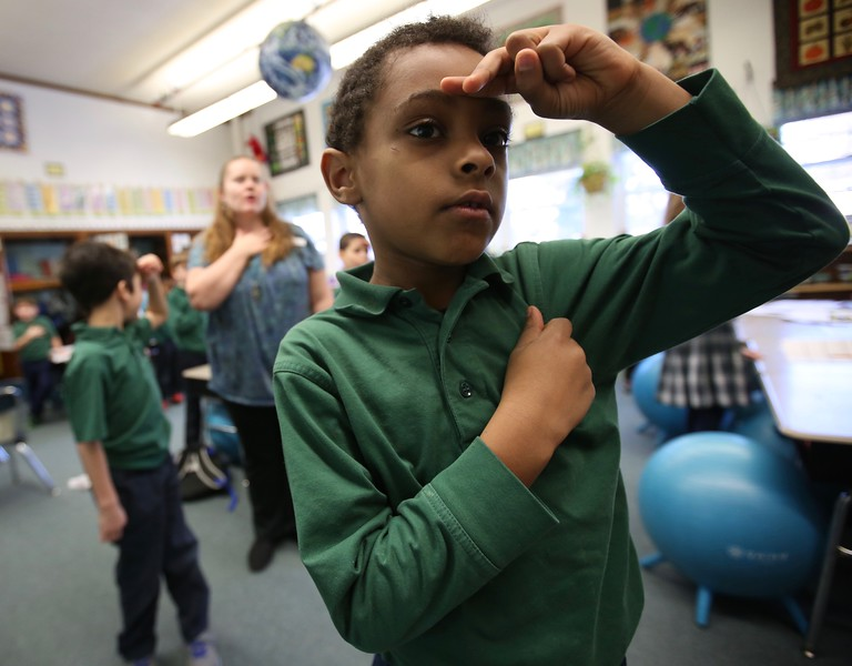 9:11 a.m. St. Peter Catholic School, North St. Paul: First-grader Yobel Halefom recites the Pledge of Allegiance with his classmates.