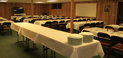 SERVING TABLE (use Chime Bell Tables).   THREE  8 foot tables set on Left back wall and SHORT table next to this Front Post.