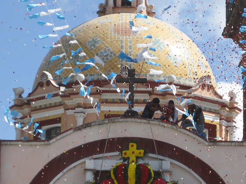 Young men throwing rose petals from the roof of the church.