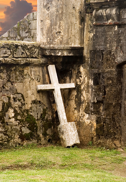 An almost white crucifix, pulled from the ground, is leaning against the walls of an old abandoned building that is slowly crumbling. The image portrays a sense of melancholy loneliness.