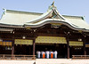 A traditional Shinto temple in Japan viewed from across a courtyard. Inside, a group of priests are lined up in the sanctuary for a morning ritual.