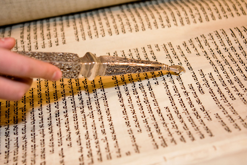 An old Torah scroll being read at a bar mitzvah with a traditional yad which is required. This ornate pointer has a finger at the end that points to the word that is currently being read.