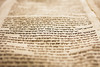 A part of the Hebrew text fomr a portion of a Torah scroll. This scroll is estimated to be 150 years old and is wrinkled and spotted with age. This view has very tight selective focus on just one line on the page with the foreground and background moving quickly to be out of focus.