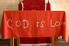 A handmade cloth saying God Is Love. This covers the altar of a make-shift church in the township of Kayamandi, South Africa.