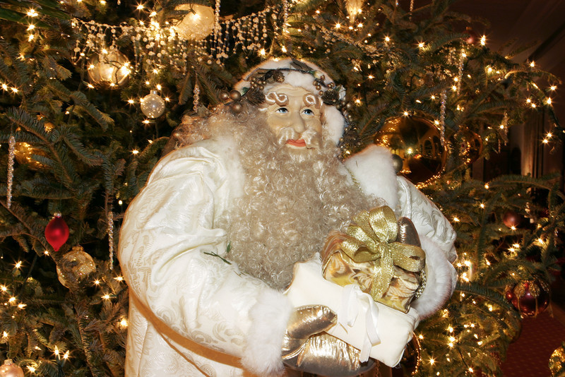 A figure of Saint Nick with a full beard and in a white robe bearing a gift. He is in front of a Christmas tree lit up with lights, gold balls, and other decorations.