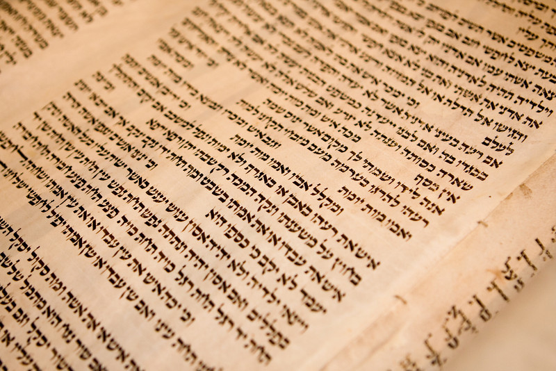 Hebrew text on one panel of a antique Torah scroll that is 150 years old. The traditional stitching holding the parchment panels together is visible.