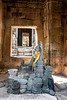 A Buddha statue, draped with a gold cloth, stands in a hallway surrounded by fallen balusters.
