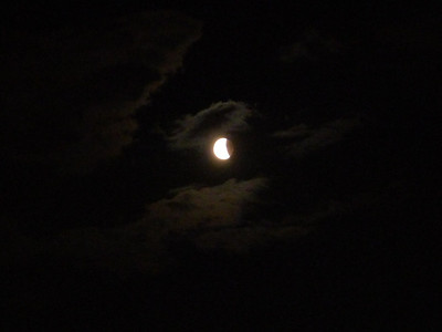 Earth shadows the moon amid clouds. 2340 local time.