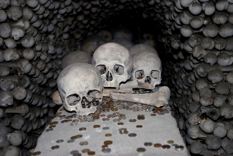 At the Sedlice All Saints bone church in Kutna Hora, a display of skulls is surrounded by donations of various coins. The walls surrounding the skulls are made of various bones from legs and arms. A scary image for Halloween.