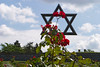 The Star of David rises over the cemetery in front of the walls of the Terezin (or Theresienstadt) prison. The flowers are planted at every grave marker.