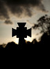 A single headstone in a cemetery in Edinburgh, Scotland is silhouetted by the setting sun at dusk.