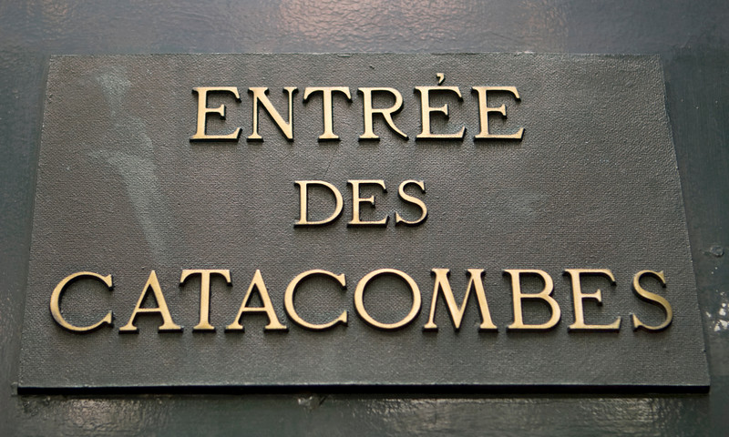 A sign in Paris announcing the entrance to the Catacombs, an underground cemetery.