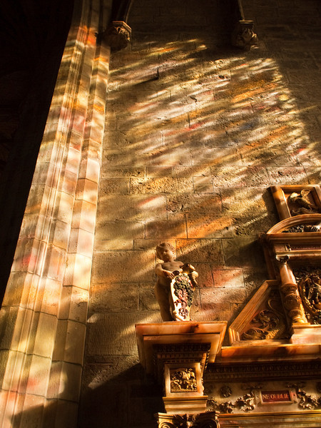 Multi-colored light from a stained glass window splashes over the wall and stonework in a chapel in St. Giles Cathedral in Edinburgh, Scotland.