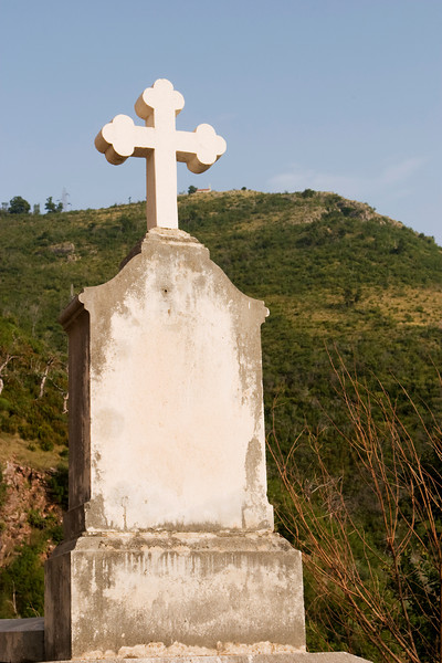 A cross on a plain, unmarked headstone raises its profile over the hillside behind it.