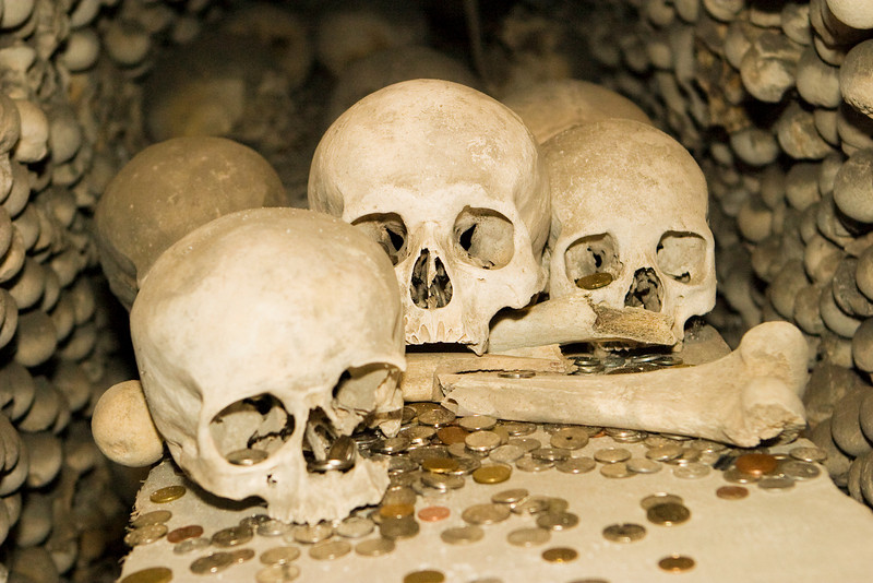 A detailed view of one of the crypts at the ossuary in Kutna Hora with skulls. Coin offerings have been tossed into the area with some landing in the eye sockets.