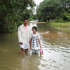 Sarin and his daughter, Vita, show how deep the water stands on this section of the road.