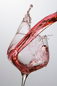 A light red wine being poured into a wine glass.