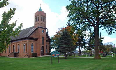 St Thomas Church on St Thomas Road in Le Sueur County. The green and white township hall for Derrynane Township can be seen in the background on the right.