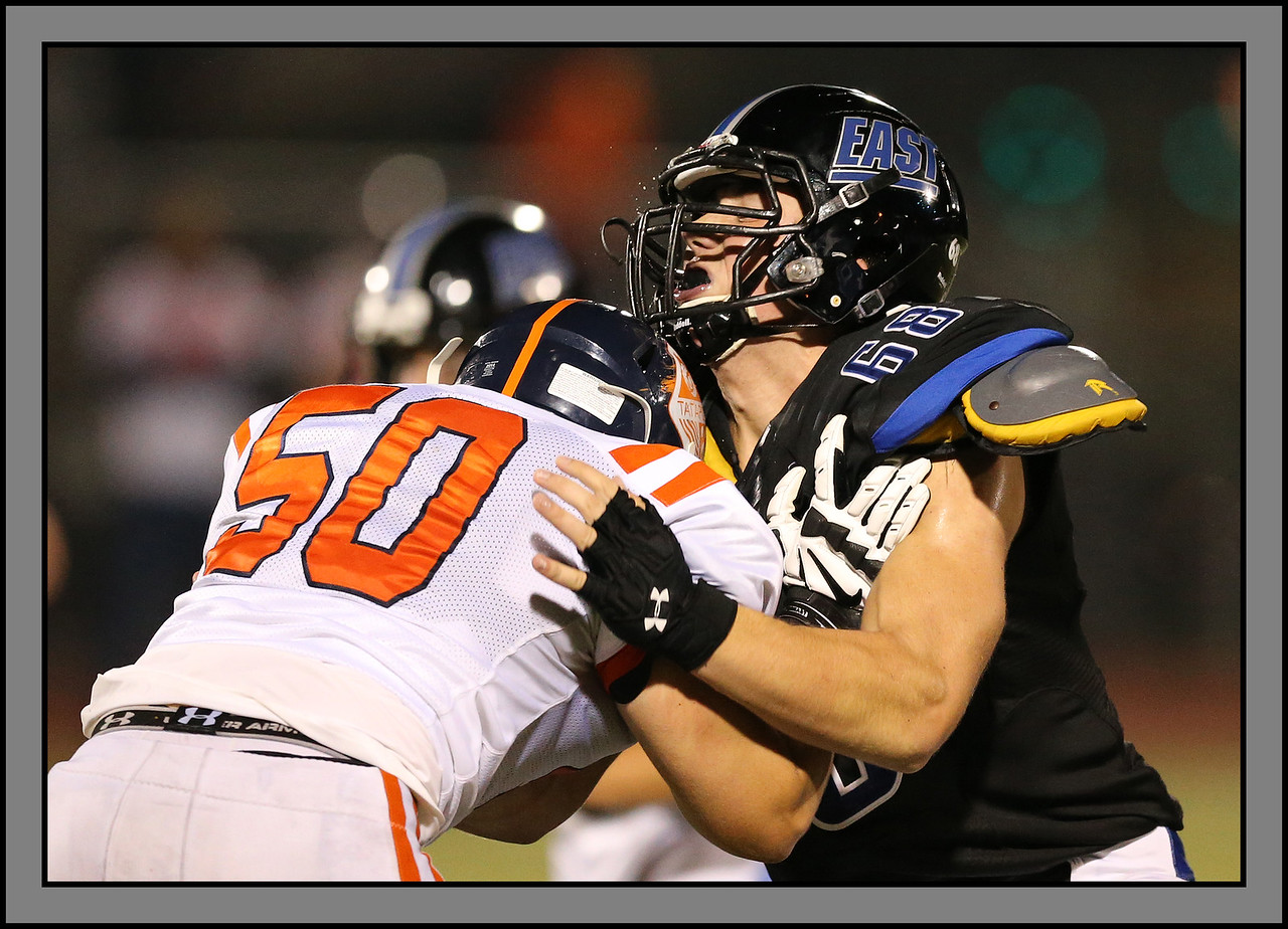 Oak Park River Forest's Nick Straka (50) and Lincoln-Way East's Tim Vyhnanek (68) battle in the line as the Huskies played the Griffins in Frankfort, Illinois, August 29, 2014. | Allen Cunningham/For Sun-Times Media