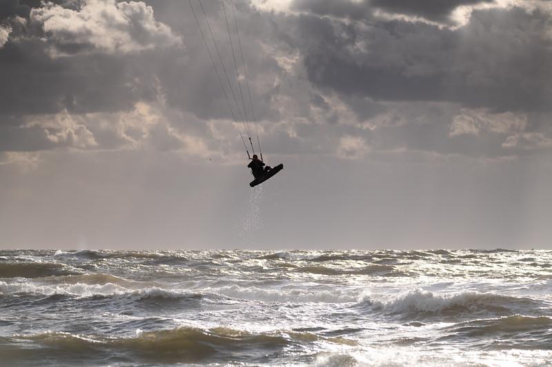 High jumping Kitesurfer with sun shining at water droplets