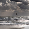 Silhouette of a jumping kitesurfer with sun coming through clouds
