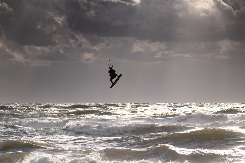 Silhouette of a jumping kitesurfer with sun reflecting in water droplets