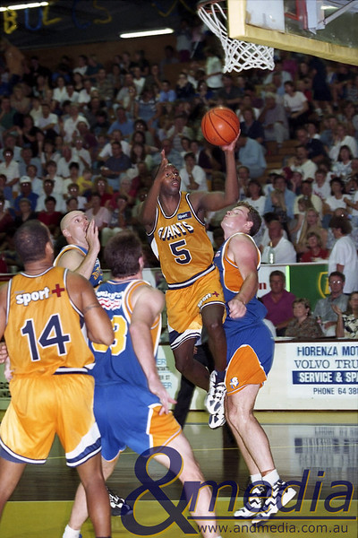 1996 091196GBGG0132A SBL - Semi Final Game 2 - Goldfields Giants @ Geraldton Buccaneers - 9th November 1996 Giants' swingman Vern Robateau lays the ball up over Geraldton centre Andrew Kennedy. Photo by Travis Anderson - Andmedia/Pro Sports Images ©1996.
