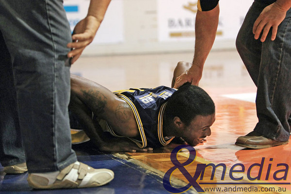 270609GGWWK6018 SBL - Goldfields Giants vs Wanneroo Wolves Giants' import Alonzo Hird lies on the edge of the court in pain after hurting his knee on a layup attempt. He is being attended to by Giants' managers Colin Earle and Randal Hulme. Photo by Travis Anderson - Andmedia/Sports Vision ©2009.