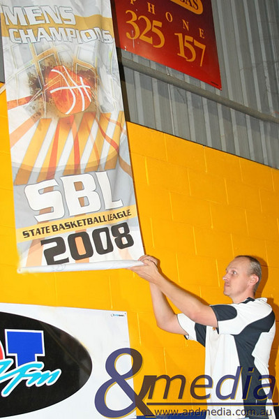 220309kalgiantsta SBL - Goldfields Giants vs Perry Lakes Hawks Goldfields Giants life member and club legend Wayne Creek unfurling the 2008 championship banner during the banner raising ceremony.