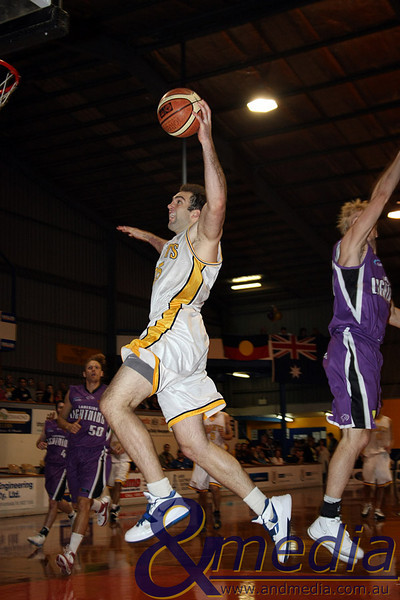 080510GGLL0055 SBL - Goldfields Giants vs Lakeside Lightning Giants' centre John Vaudreuil flies past Lakeside swingman Luke Payne on his way to the basket. Photo by Travis Anderson - Andmedia ©2010.