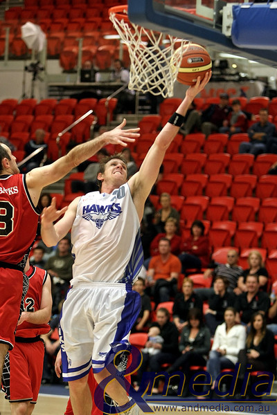 050610PHPR1622 SBL - Perry Lakes Hawks vs Perth Redbacks - 5th June 2010 Hawks' guard Peter Crawford avoids the outstretched arm of Redbacks' guard Ryan Neill as he drives in for the layup. Photo by Travis Anderson - Andmedia ©2010.