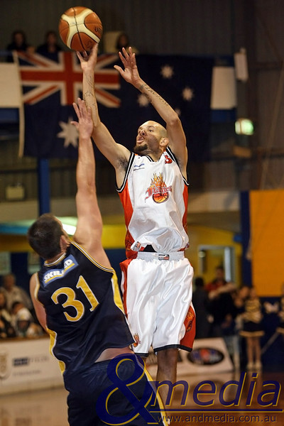 120610GGRF1171 SBL - Goldfields Giants vs Rockingham Flames - 12th June 2010 Flames' forward Demetrius Hazel launches a three point attempt over the Giants' Michael Haney. Photo by Travis Anderson - Andmedia ©2010.
