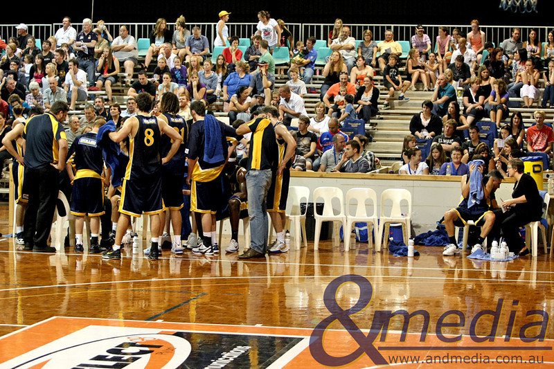 260311GGEE10323 SBL - Goldfields Giants vs East Perth Eagles Giants' co-captain Ryan Hulme has his nose injury treated by team trainer Gen Major (far right) as the rest of the team huddles during a time out. Photo: Travis Anderson - Andmedia/Sports Vision ©2011