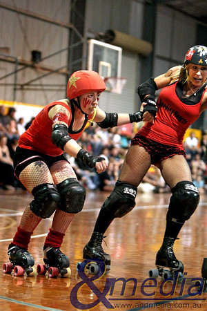 130211GCRD0048 Gold City Roller Derby Presents... The Bloody Valentine Bout - Bleeding Hearts vs Rotten Candy @ Neils Hansen Stadium - 12th February 2011 Kalgoorlie derby girl Shifty Swifty (left) receives a whip from her Bleeding Heart teammate Hot Wheels. Photo: TRAVIS ANDERSON - Andmedia ©2011.
