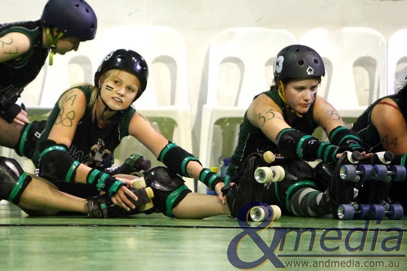 210511PRD12343 Perth Roller Derby present - Quads of War Bout #2: PRD Allstars vs WARD's of the Skate @ Midvale Speed Dome, 21st May 2011. WARD skaters Steely Niel and Juicy M. Suffer stretch up before the bout. Photo: TRAVIS ANDERSON - Andmedia ©2011.