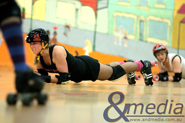 """051010GCRD5479 Gold City Roller Derby training - 5th October 2010 """"Bang Bang Lou Lou"""" and """"Loopy Loo"""" hold tight in The Plank during an exercise. Photo - Andmedia ©2010."""