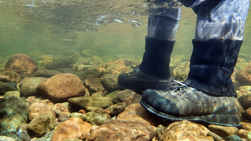 Underwater view of fly fisherman wading in river.