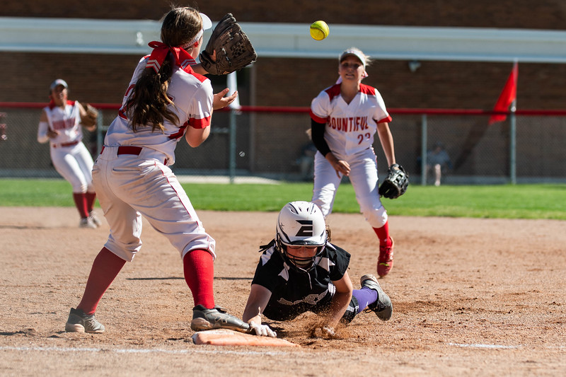 Katie Tanner (23), of Bountiful High, throws the ball to her teammate, Abby Steed (27), trying to catch Box Elder player, Reagan Marziale (4), off of the base, at Millcreek Junior High, in Bountiful, on May 8, 2018.
