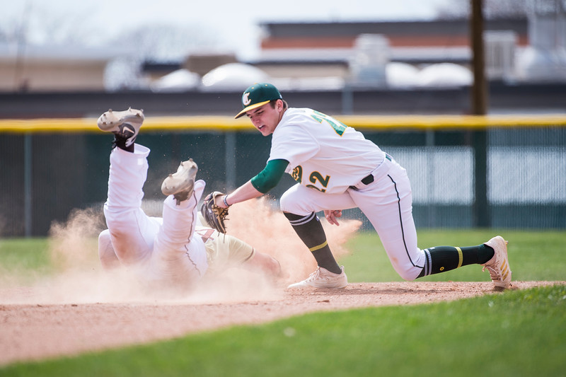 Clearfield player, Jaxon Mansfield (22), barely misses the tag on Davis player, Zach Hoskins (24), at Clearfield High School, in Clearfield, on Friday, April 20, 2018.