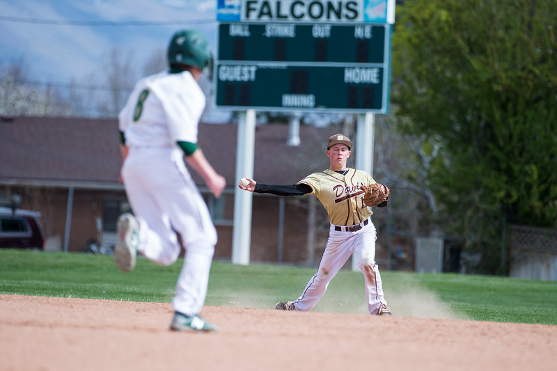 Parker Jensen (10), of Davis High, fields a grounder and gets out Brady Ross (8), of Clearfield High, at second base at Clearfield High School, in Clearfield, on Friday, April 20, 2018. Jensen made the play immediately after colliding violently with a Clearfield player and taking several minutes to get back to his feet.
